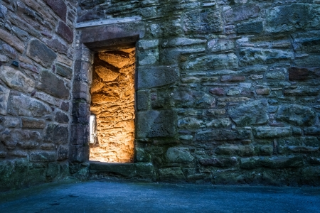 castle interior: Lighted dorway to the ancient castle Stock Photo
