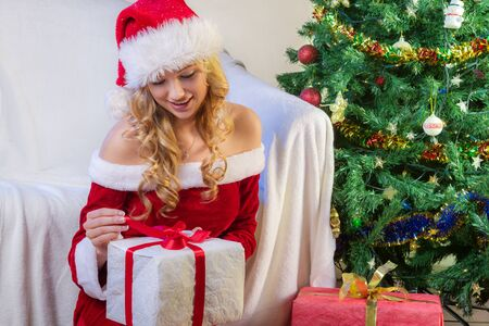 Christmas gift, tree and beautiful young woman in red dress photo