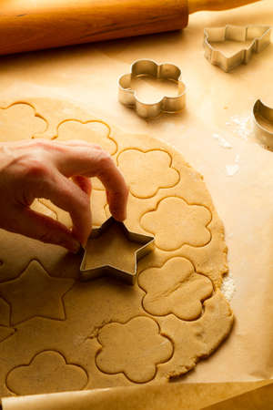 Cutting of Christmas cookies on baking paper photo