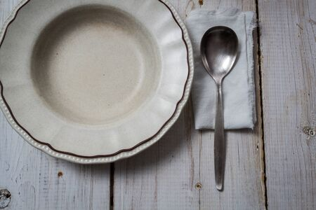 Old empty plate and spoon on wooden table photo