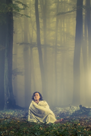 Lost woman in a dark misty forest photo