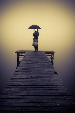 Lonely woman protected by an umbrella on bridge photo