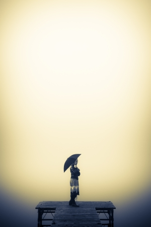 Lonely woman looks to the misty lake Stock Photo