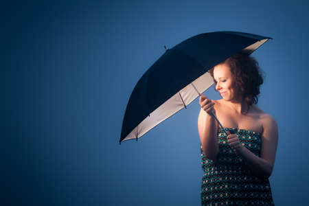 Joyful woman protected by an umbrella on a cold day photo