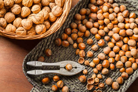 Hazelnuts and walnuts with in wicker basket on old table Stock Photo - 16397564