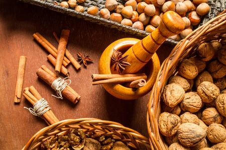 Closeup to walnuts, hazelnuts and cinnamon in wicker baskets Stock Photo - 16397554
