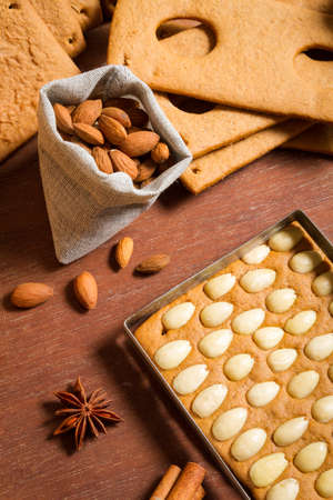 Close-up on almonds and gingerbread cottage elements photo