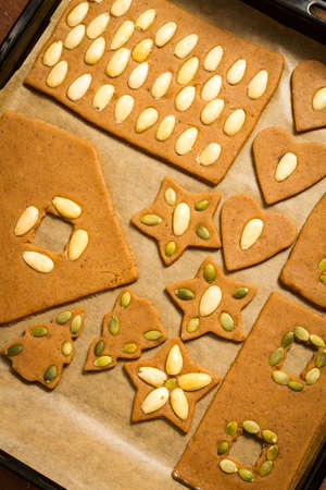 Gingerbread cookies on baking tray decorating with nuts Stock Photo - 16397566