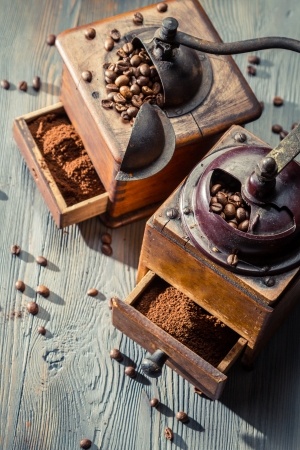 Two old coffee grinders on wooden table photo