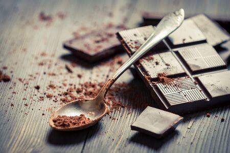chocolate bar: Cocoa Powder on spoon and Dark Chocolate background