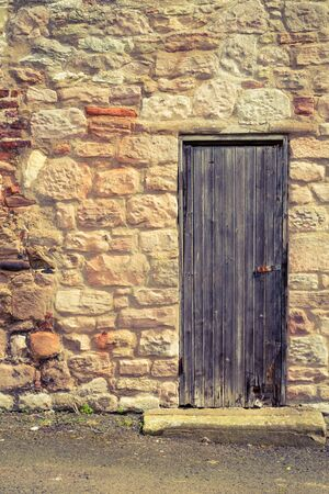 Old vintage wooden door in stone wall photo