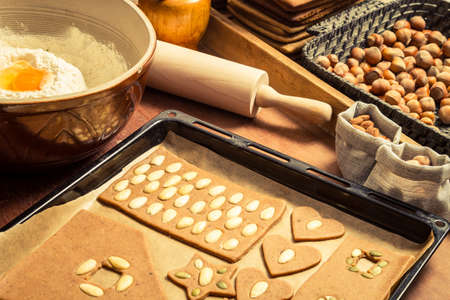 Decorating gingerbread cookies nuts just before baking Stock Photo - 16824143