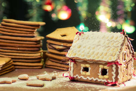 Decorating gingerbread cottage on Christmas tree background photo