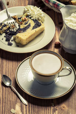 Coffee with milk and poppy seed cake on old table photo