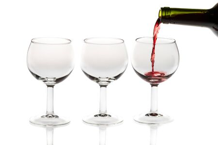 filling bottles: Pouring red wine into glass from bottle on white background