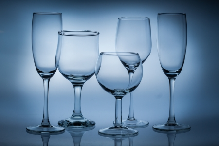 Different types of empty glasses on a blue background photo