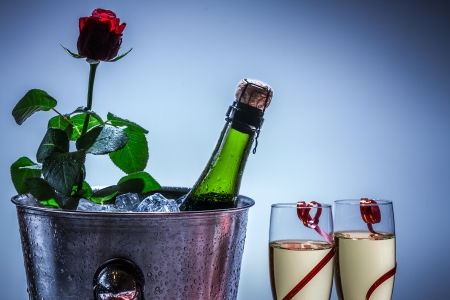 Red rose and champagne in ice cold photo