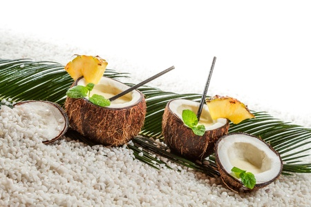 Few pinacolada drinks in coconut on white beach photo