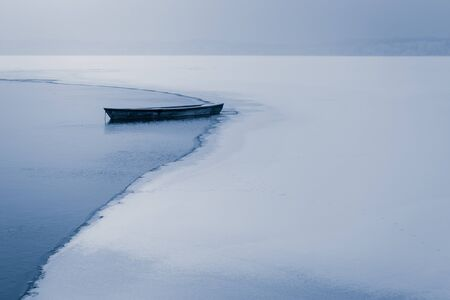 Alone boat on frozen lake in winter photo
