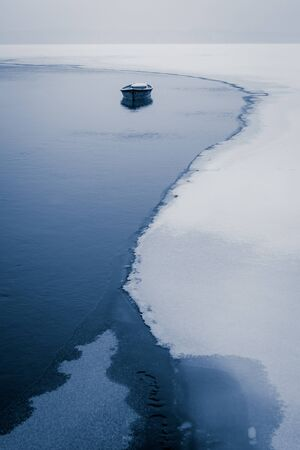 Alone boat on frozen river in winter photo