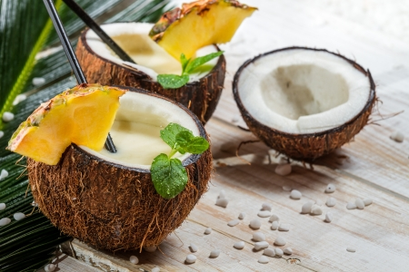 caribbean drink: Pinacolada in a coconut on old white table