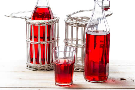 Closeup of red juice in old bottles on white background photo