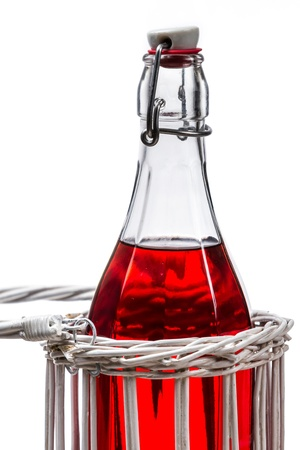 Odl bottle with red juice on white background photo
