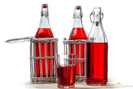Vintage bottles with red juice on white old table photo