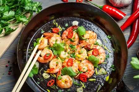 Closeup of shrimps on pan with fresh herbs photo