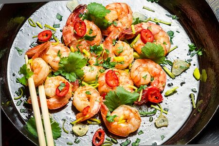 Shrimps sauteed with garlic and butter on pan photo