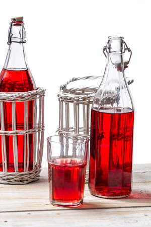 Bottles in basket with red juice on white background photo