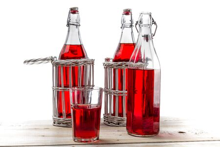 Vintage bottles with red juice on white background photo