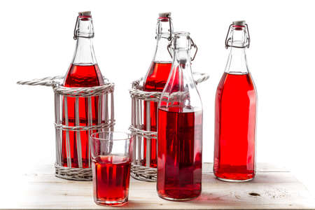 Bottles with red juice on white background photo