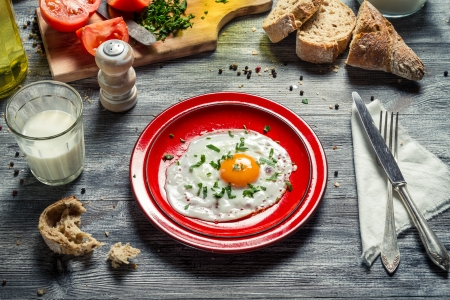 Fried egg for breakfast with bread and vegetables photo