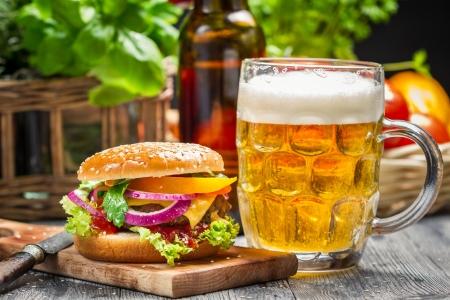 hamburguesa de pollo: Primer plano de hamburguesa fresca y una cerveza fr�a