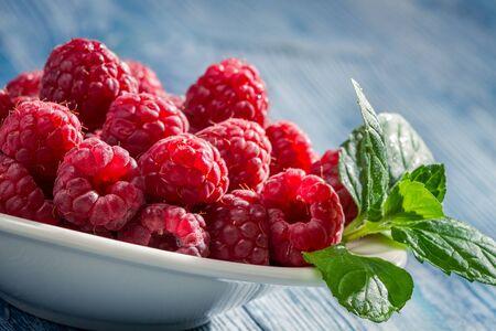 Closeup of fresh raspberries with green leaf photo