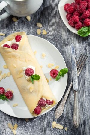Raspberry pancakes with almonds and icing sugar photo