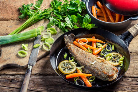 Freshly fried fish with leek and carrot photo