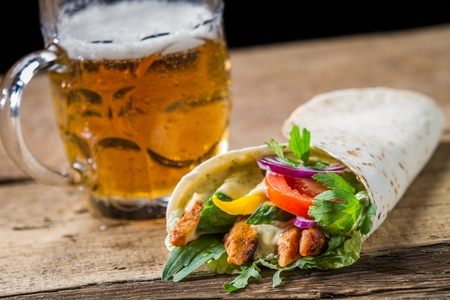 Kebab served with cold beer on old wooden table photo