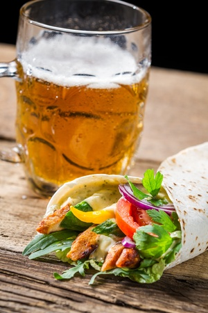 Tasty kebabs and cold beer on old wooden table photo