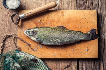 Preparing freshly caught trout on an old wooden chopping board Stock Photo - 18889623