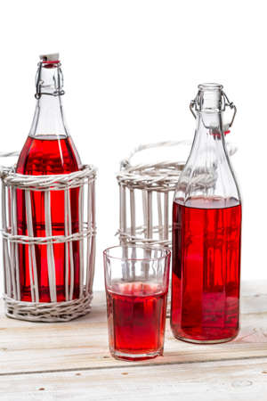 Red juice in bottles on white background photo