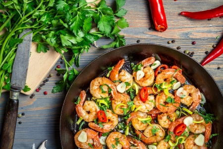 european food: Shrimps fried on pan with fresh herbs