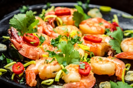 Fresh shrimps on old pan with garlic