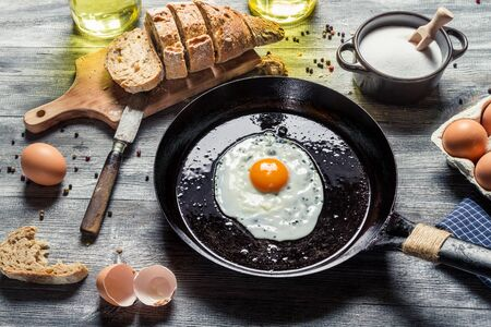 fried egg: Fried egg on a pan served with homemade bread