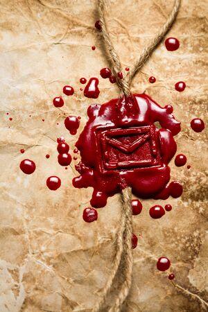 Closeup of envelope symbol imprinted in red sealing wax