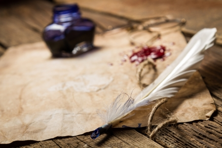 Closeup of a feather lying on old sheet of paper Stock Photo - 19439471