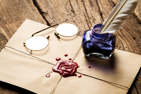 Inkwell with feather on envelope with red sealant and glasses Stock Photo - 19439472
