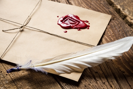 Closeup of feather on envelope with red sealant Stock Photo - 19439477