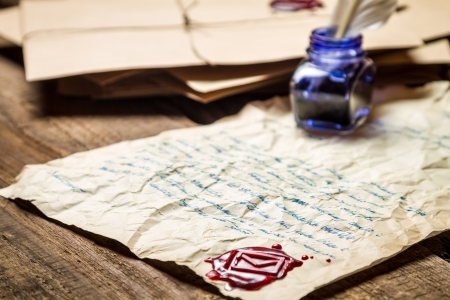 beeswaxseals: Inkwell with blue ink andsealing wax on the background of vintage letters